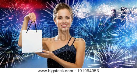 shopping, luxury, advertisement, holydays and sale concept - smiling woman with white blank shopping bag over nigh city and firework background