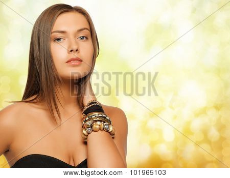 beauty, luxury, people, holidays and jewelry concept - beautiful woman with bracelets over yellow lights background