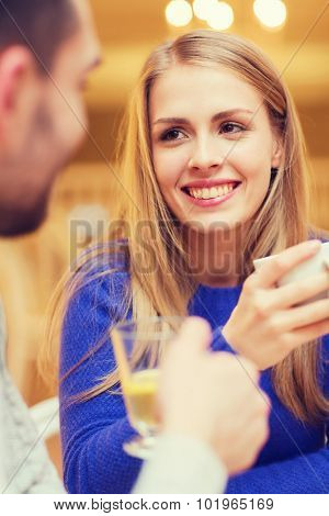people, leisure, dating and communication concept - happy couple dating and drinking tea at cafe or restaurant
