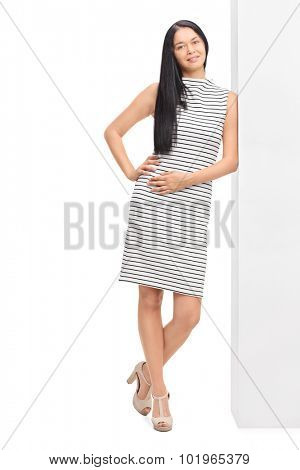 Full length portrait of a woman in a white dress with black stripes leaning against a wall and looking at the camera isolated on white background