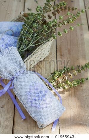 Sachet with ukrainian embroidery, sheaf of wheat and dried herbs on wooden background, close-up sele