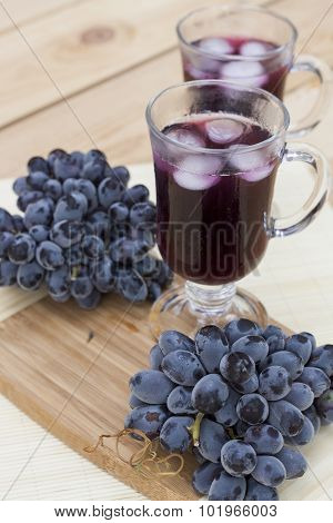Grape juice cooler with ice in glass and glass of fresh blue grapes on a wooden table close-up
