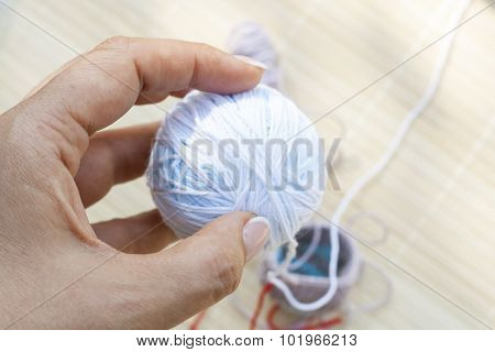 Color woolen clews for knitting in hand close-up, selective focus