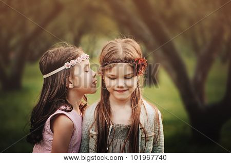 two cute little girls telling secrets to each other in summer park, friendship concept
