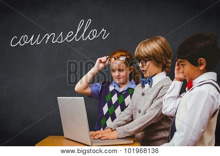 The word counsellor and pupils using laptop against blackboard