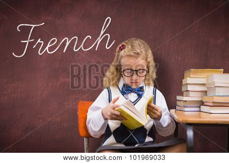 The word french and blonde pupil reading a book against desk