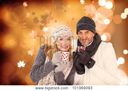 Portrait of couple drinking hot coffee against autumnal leaf pattern
