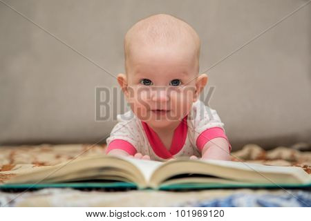 Baby lying on the belly reading a book