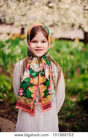 spring portrait of adorable happy child girl in tradition shawl at blooming apple tree