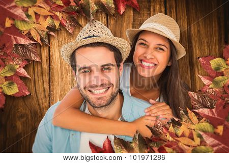 Happy casual man giving pretty girlfriend piggy back against wooden table