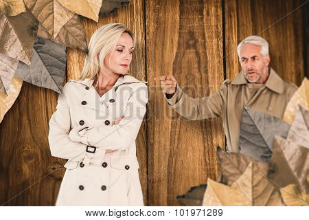Angry husband pointing wife against wooden table