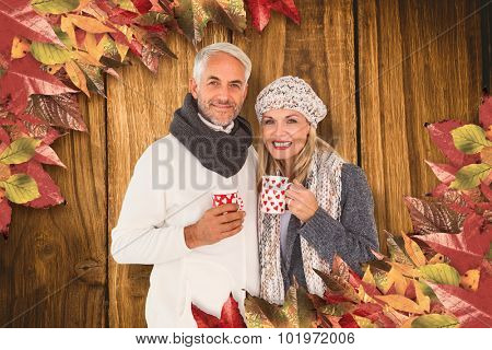 Portrait of happy couple drinking hot coffee against wooden table