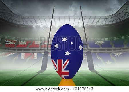 Australian flag rugby ball on stand against rugby pitch