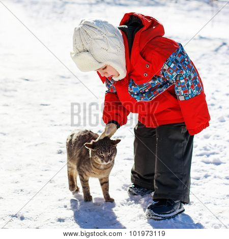 Little Boy Playing With Cat Outdoors In Winter