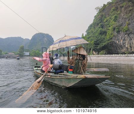 People Rowing Boats For Carrying Tourists In Tam Coc