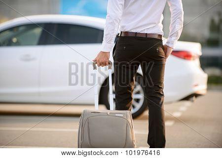 Nice businessman holding suitcase