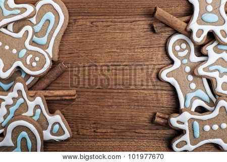 Gingerbread cookies with cinnamon sticks on a wooden background