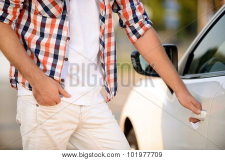 Young man opening his car