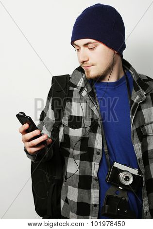 life style, tehnology and people concept: cheerful man in shirt and  hat using smartphone  on gray background