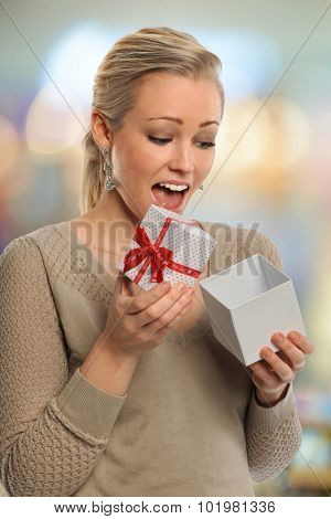 Young woman reacting with surprise when opening gift box