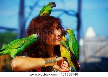 Young woman in ornamental dress and beautiful gold jewelry with a color parrots. woman kiss bird.