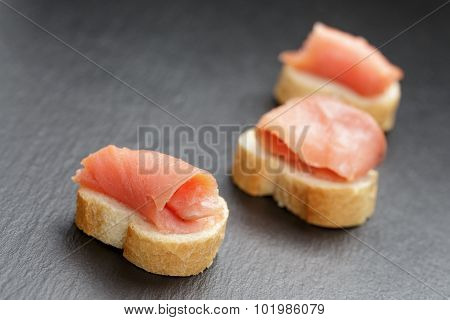 baguette slices with curred salmon on slate