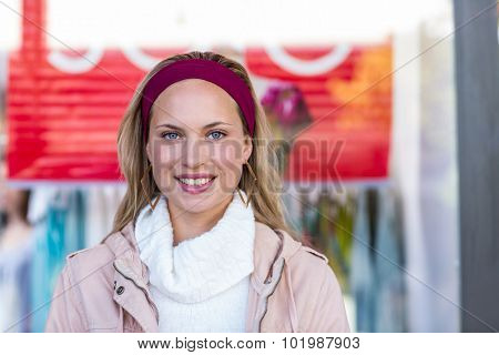 Portrait of smiling woman in front of sale sign at shopping mall