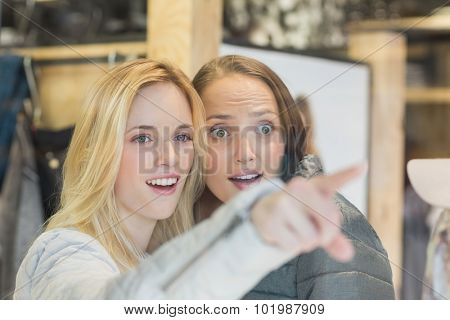 Two astonished female friends pointing away in clothes store