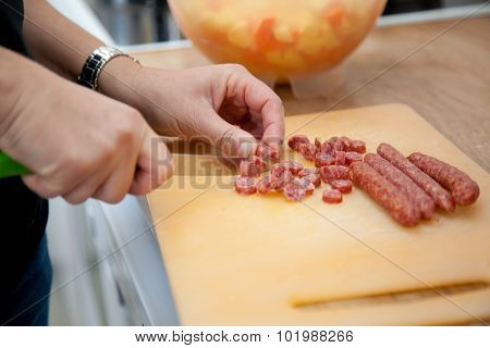 Woman Chopping Salami Sticks In The Kitchen