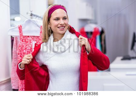 Smiling woman putting on red coat in clothing store