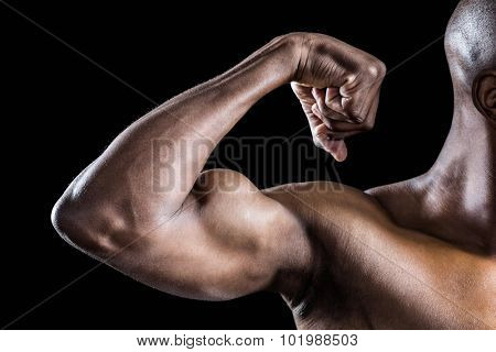 Cropped image of muscular man flexing muscles against black background