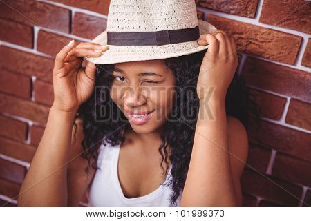 Hipster winking at camera on red brick background