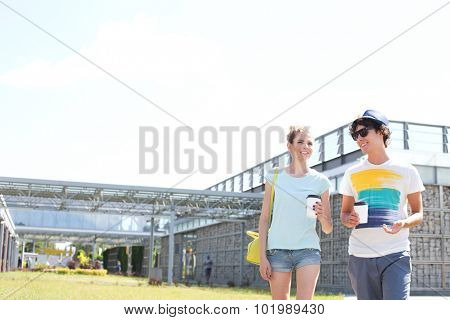 Smiling couple holding disposable cups while walking at park