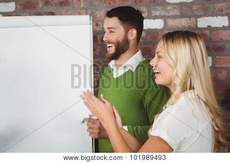 Businesswoman clapping with male colleague in background