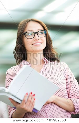 Smiling woman looking away while holding book outdoors