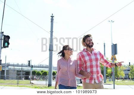 Happy couple walking in city against clear sky