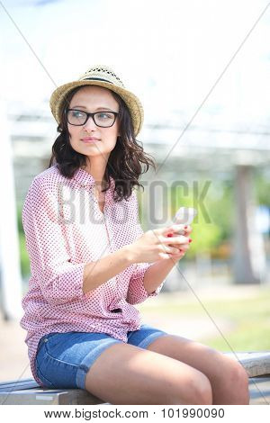 Woman looking away while holding mobile phone on bench outdoors