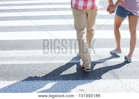 Low section of couple walking on crosswalk