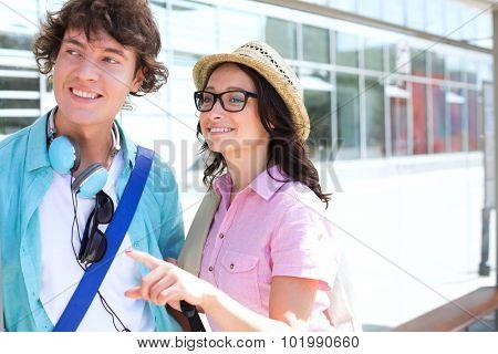 Smiling woman showing something to man while waiting at bus stop