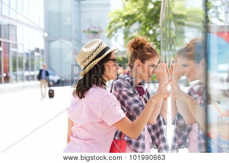 Happy female friends window shopping in city