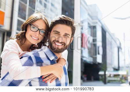 Portrait of happy man giving piggyback ride to woman in city