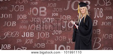 Blonde student in graduate robe holding a diploma against desk
