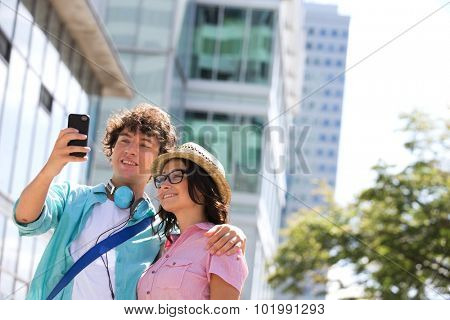 Smiling couple taking self portrait outside office building