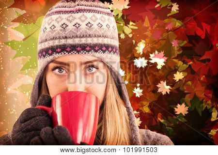 Happy blonde in winter clothes holding mug against autumnal leaf pattern