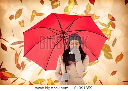 Sick brunette blowing her nose while holding an umbrella against autumnal leaf pattern in warm tones