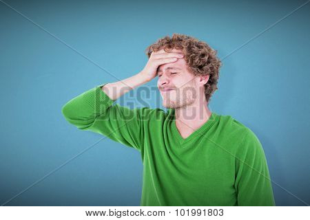 Anxious casual man standing with hand on forehead against blue background