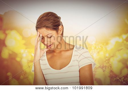 Upset woman suffering from headache against autumn scene