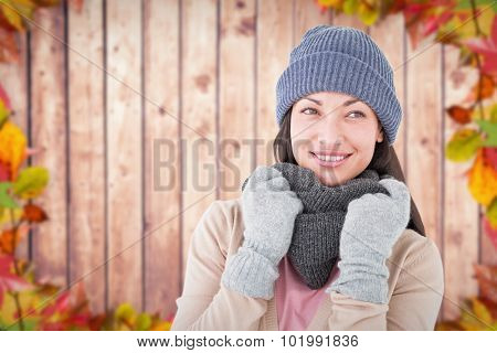 Smiling brunette wearing warm clothes against autumn leaves on wood
