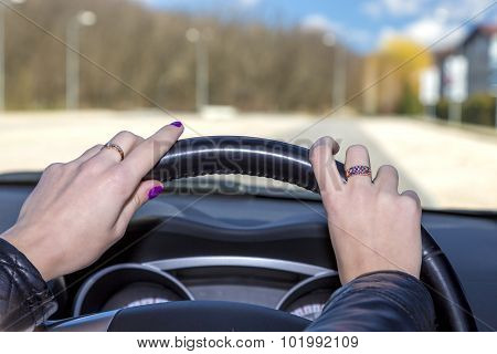Hands of female driver on steering wheel