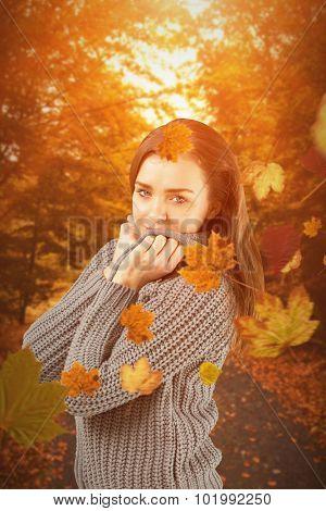 Pretty girl in winter jumper smiling at camera against autumn scene